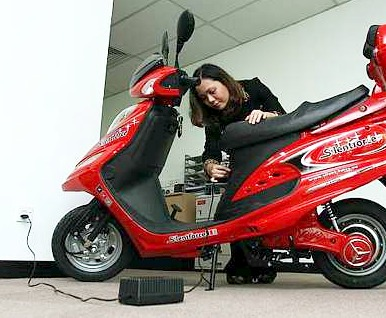 Plug in and ride: Silent Force manager Ilyia Kamaruzaman showing how to charge the scooter yesterday.