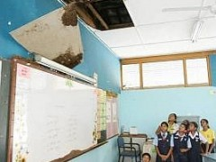 Classroom panic: Premah and her pupils looking at the ceiling which had collapsed into their classroom at SJK (T) Serdang yesterday.
