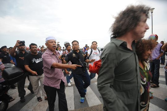 The men from the right-wing Malay group are seen chasing the British couple who happen to be near the Speakers' Square, as the police look on (far left).